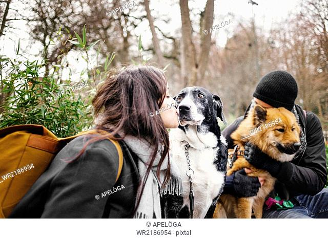 Loving young couple with dogs at park