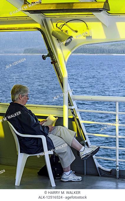 Senior tourist reading a book in the solarium of the Alaska Marine Highway MV LeConte, Southeast Alaska; Alaska, United States of America
