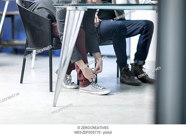 Man tying sneakers under desk