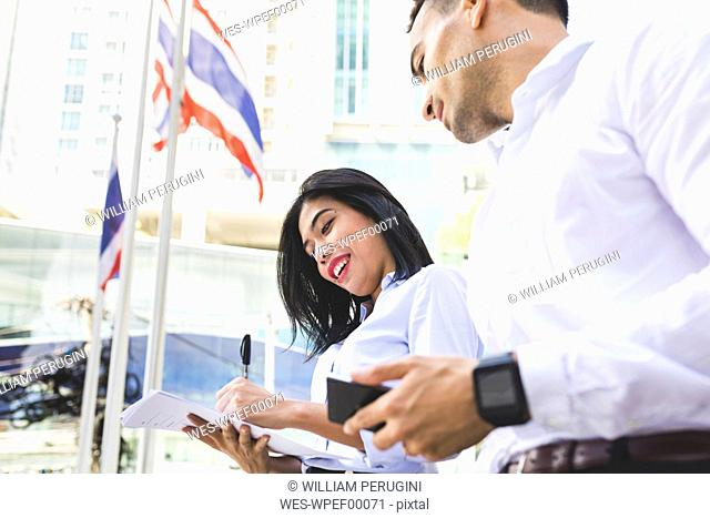 Thailand, Bangkok, businessman and businesswoman in the city with documents, cell phone and smartwatch