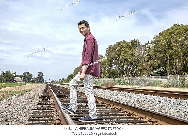 Young male standing on railway tracks, Carlsbad, California