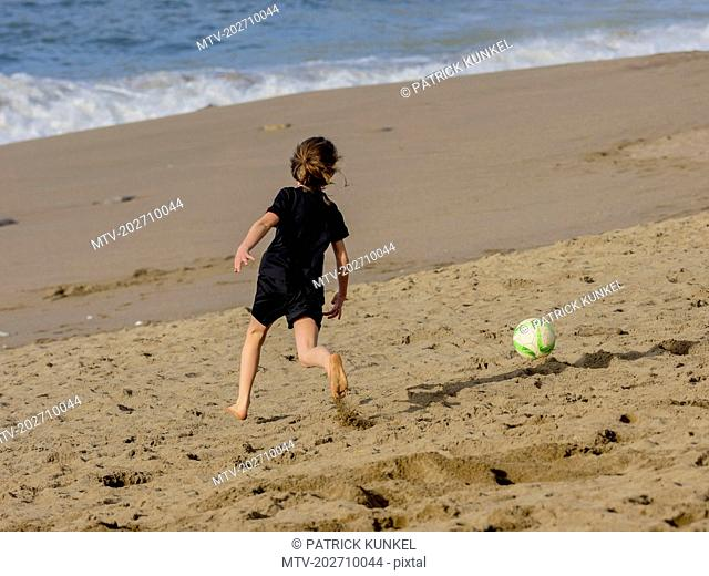 Girl playing soccer on shore at beach