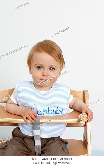 Toddler eating in highchair, Berlin, Germany