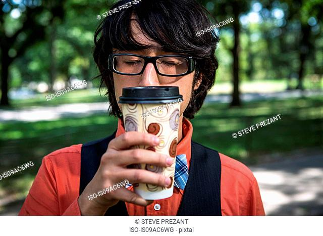 Young man inhaling coffee from disposable cup