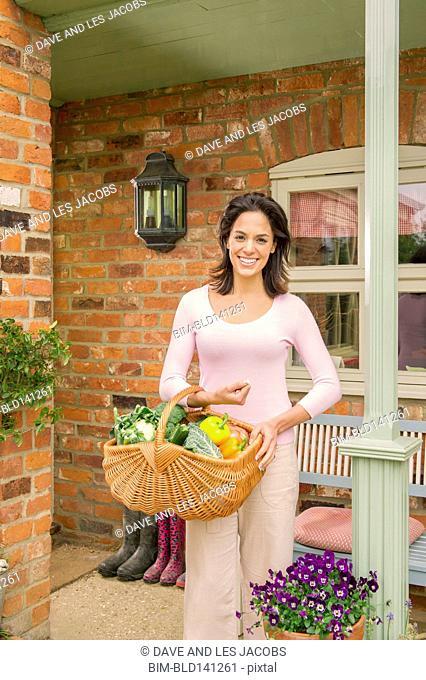 Hispanic woman carrying basket of produce on patio