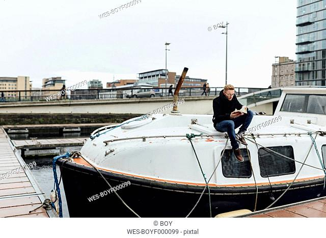 Ireland, Dublin, young man sitting on a motorboat reading a book
