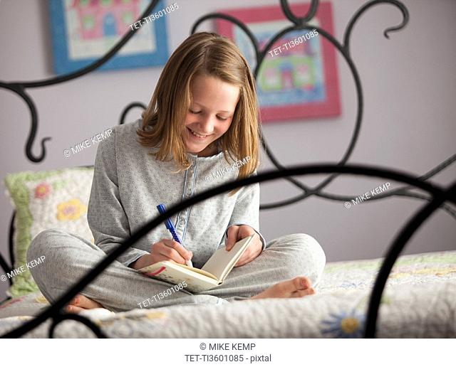 Young girl writing in her diary
