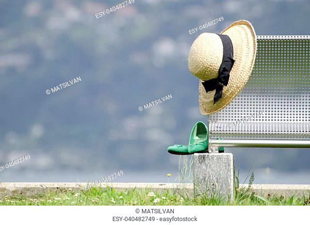 Straw hat and green shoes on a bench