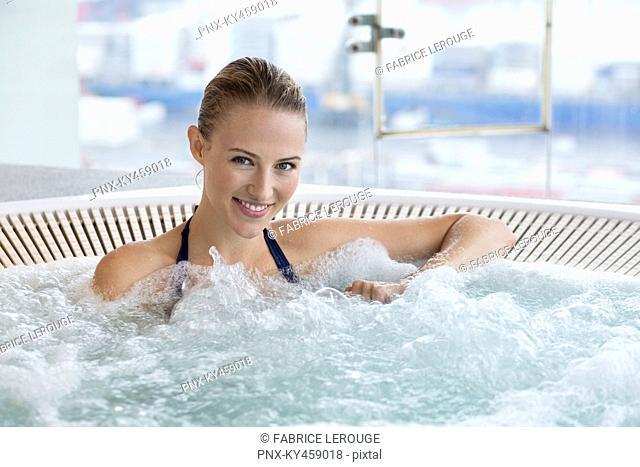 Portrait of a beautiful smiling woman in a hot tub
