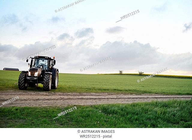 Tractor on grassy field against sky