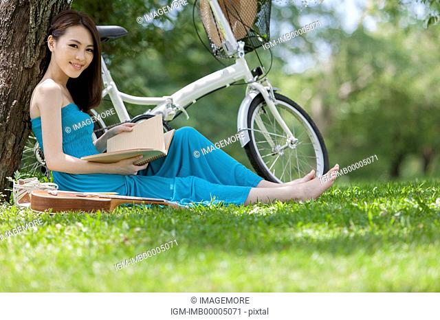 Young woman sitting on the lawn and holding a book with smile