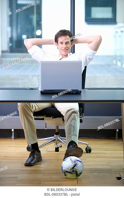 office worker working with laptop computer having football under the table