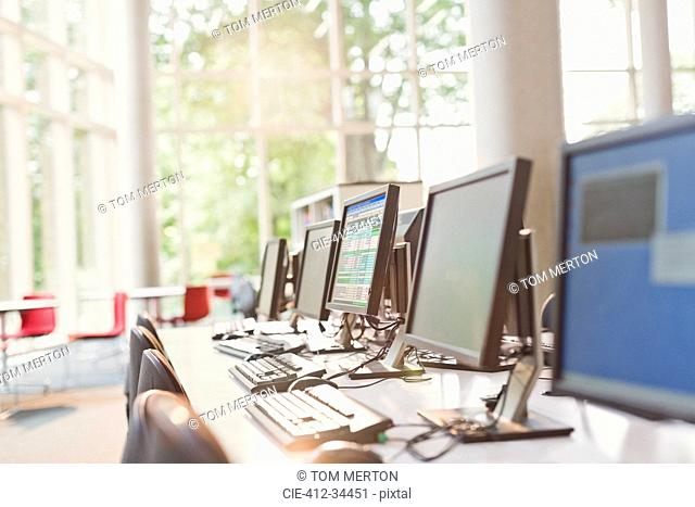 Computers in a row in sunny library office
