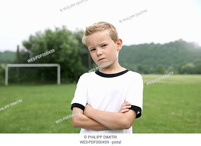 Confident boy in soccer jersey on soccer pitch