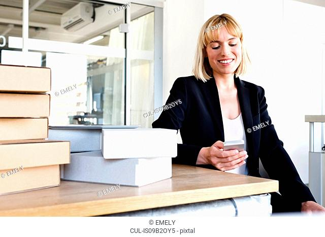 Business woman in office looking at smartphone smiling