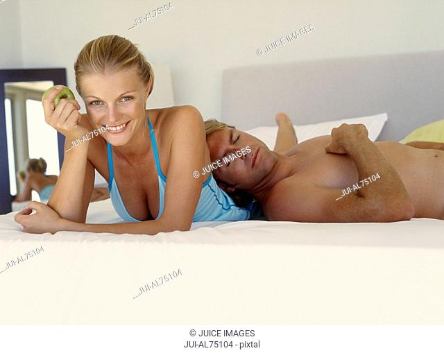 Portrait of a young man asleep on his girlfriend's back