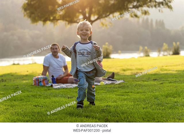 Happy boy running on meadow with family in background
