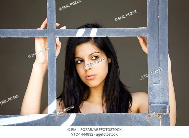 Attractive young woman portrait framed behind a metal frame