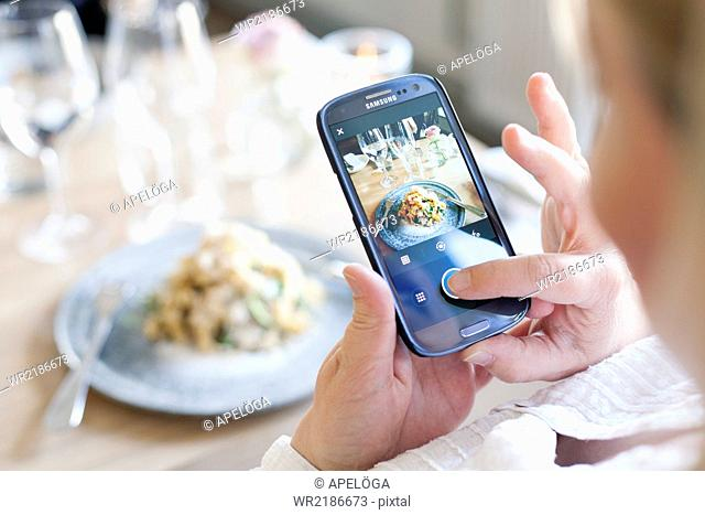 High angle view of woman photographing smoked Jerusalem artichoke at restaurant table