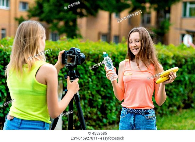 For girl schoolgirls, summer in nature. Records a video about healthy eating. In hands holding a banana bottle with water. Use camera with tripod
