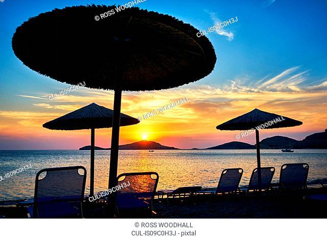 Beach umbrellas and sun loungers at sunset, Limnos, Khios, Greece
