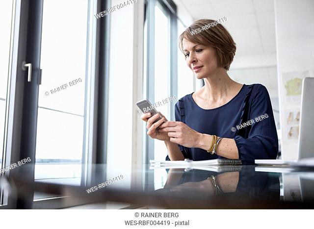 Businesswoman looking on cell phone at office desk