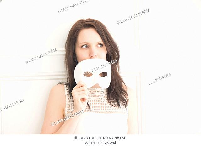 Woman holding white face mask. Concept of identity, mischief, and fun. Playful lifestyle moment