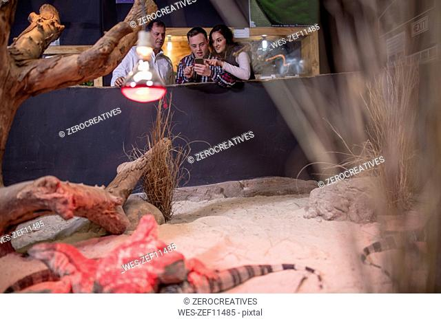 Young man with down syndrome and family at reptile exhibition