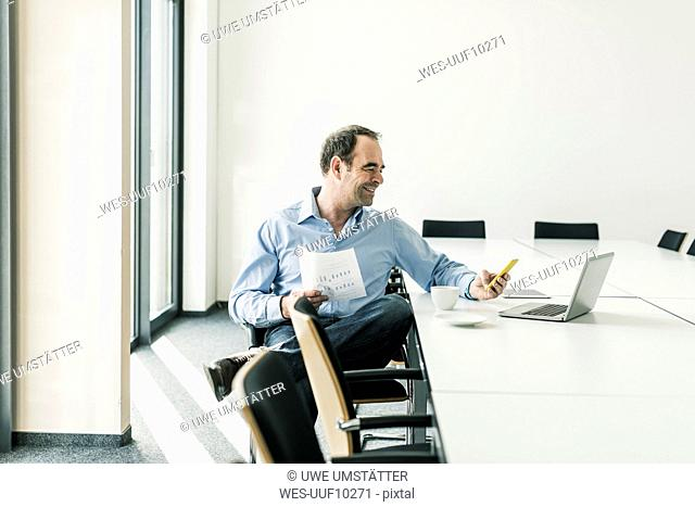 Confident businessman using cell phone in conference room