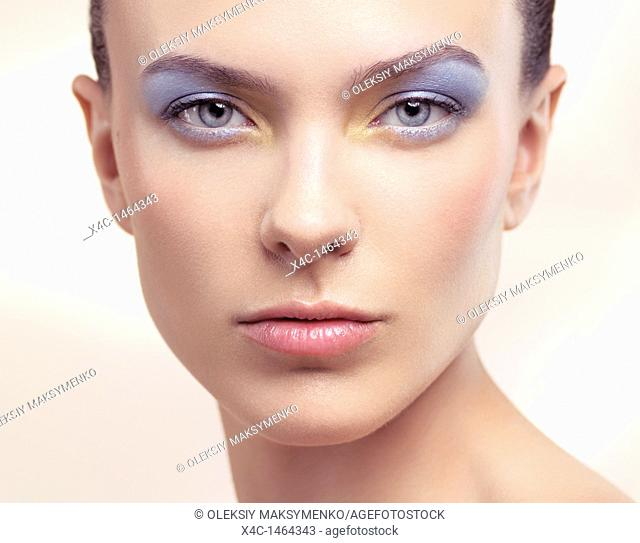 Closeup beauty portrait of a young woman face with soft pastel blue color makeup