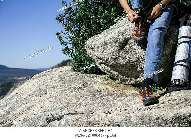 Hands of a climber tying the laces of his shoes sitting on a rock