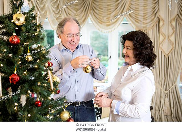 Senior couple decorating Christmas tree together