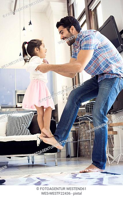 Father balancing his daughter on his foot