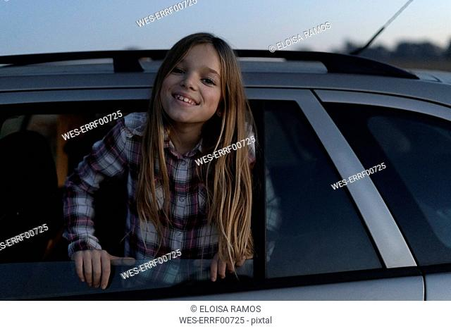 Portrait of smiling girl leaning out of car window in the evening