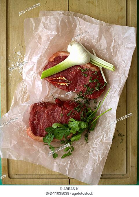 Raw beef steaks with garlic and herbs