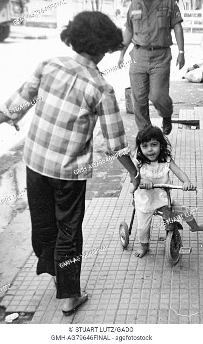 A young child riding a tricycle on a sidewalk with a woman helping her, a soldier is walking on the sidewalk in the background, Vietnam, 1967