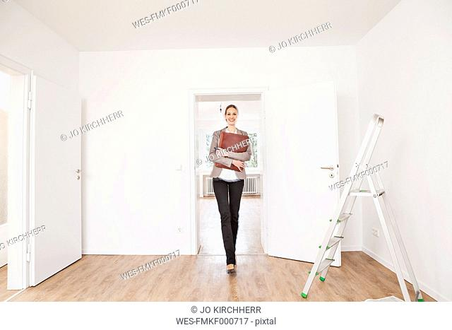 Woman with file walking on floor, smiling