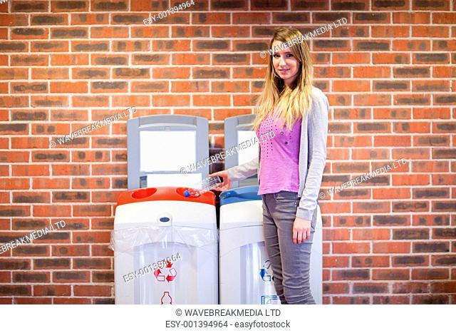 Cute woman recycling a plastic bottle