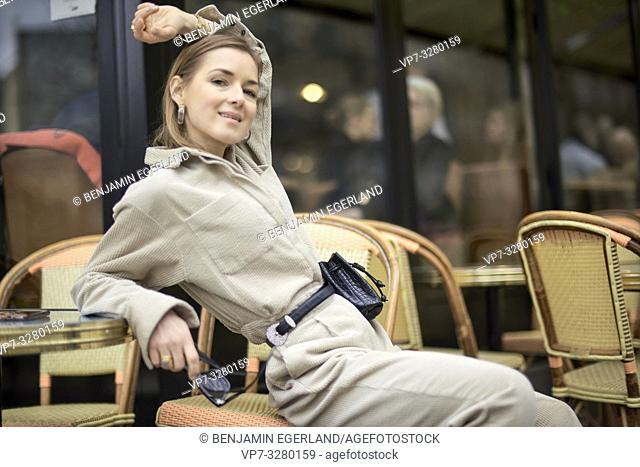 fashionable woman sitting on chair in café, in Paris, France