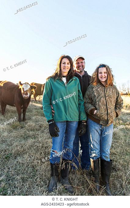 Farmer couple and daughter with grass fed cattle on their farm; Grannis, Arkansas, United States of America