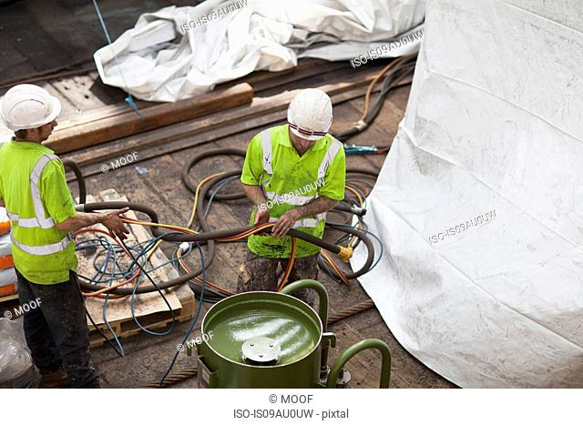 High angle view of workers lifting hose in shipyard