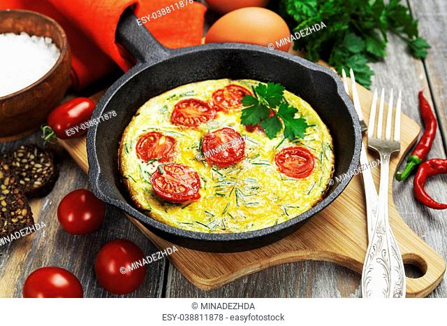 Scrambled Fried eggs with tomatoes in a cast iron pan on the table