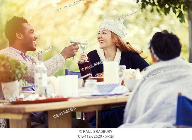 Couple toasting wine glasses at patio lunch table