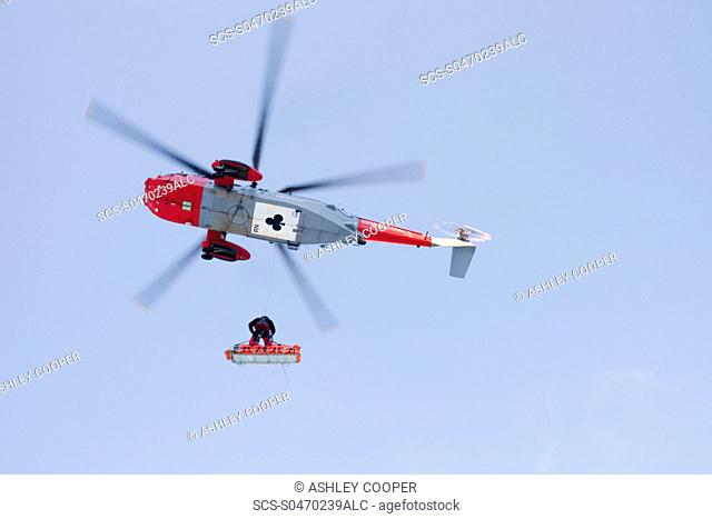 A Royal Navy Sea King helicopter evacuates a seriously injured walker who had fallen 250 feet on bow Fell in the Lake district UK