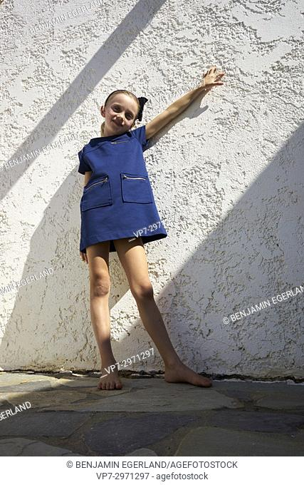 candid child posing in sunlight in front of house wall. Australian ethnicity
