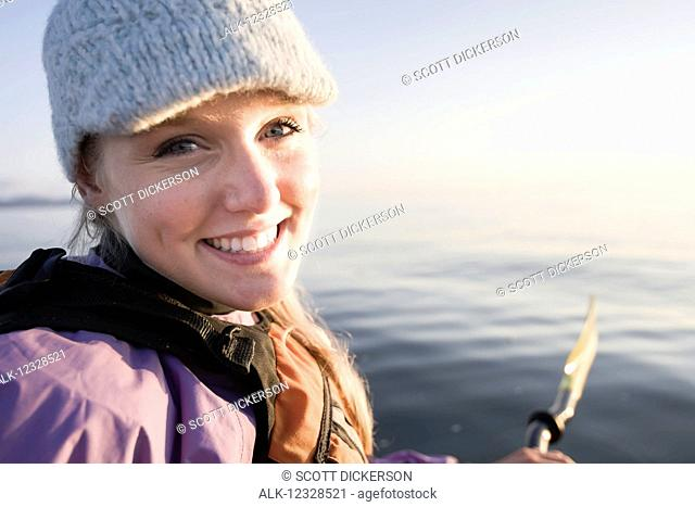 Close-up portrait of a young woman sea kayaking in Kachemak Bay, near Homer, South-central Alaska; Alaska, United States of America