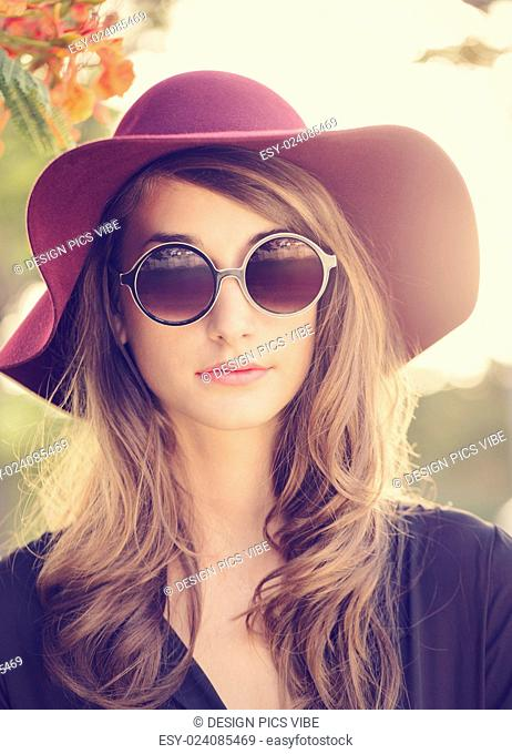 Fashion portrait of beautiful young woman in hat and sunglasses, bright warm sunny colors