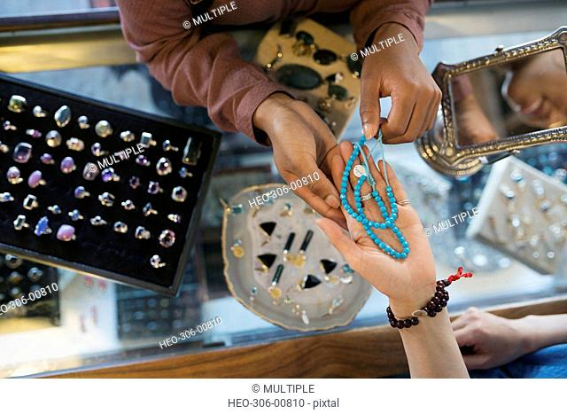 Overhead view women browsing necklace at jewelry counter in shop