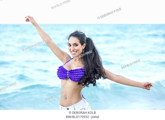 Hispanic woman playing in ocean