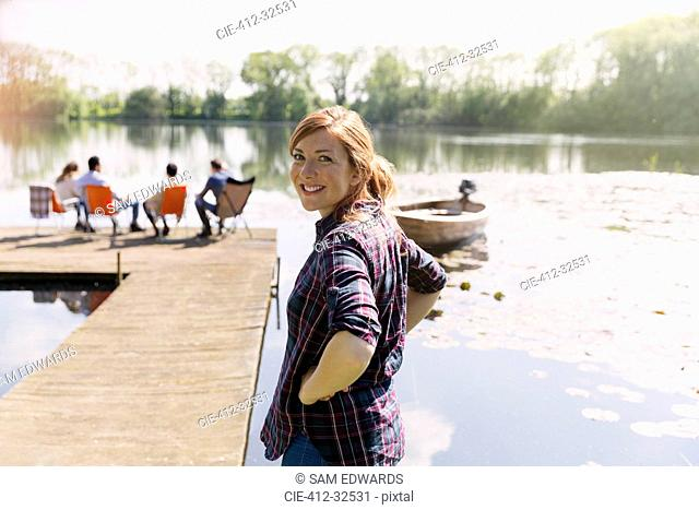 Portrait smiling woman at sunny lakeside dock